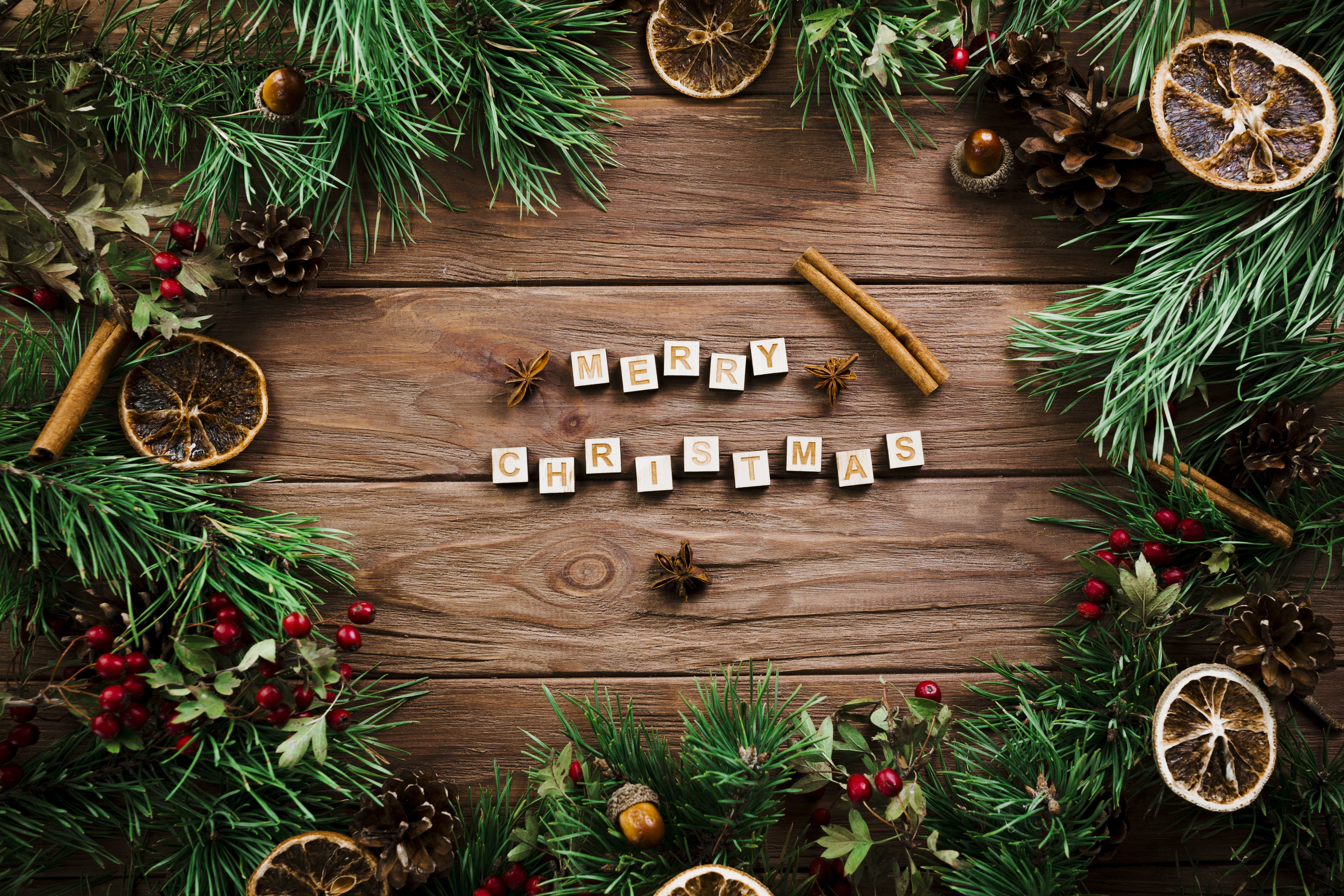 Wallpaper Merry Christmas lettering on a wooden table with fir branches.