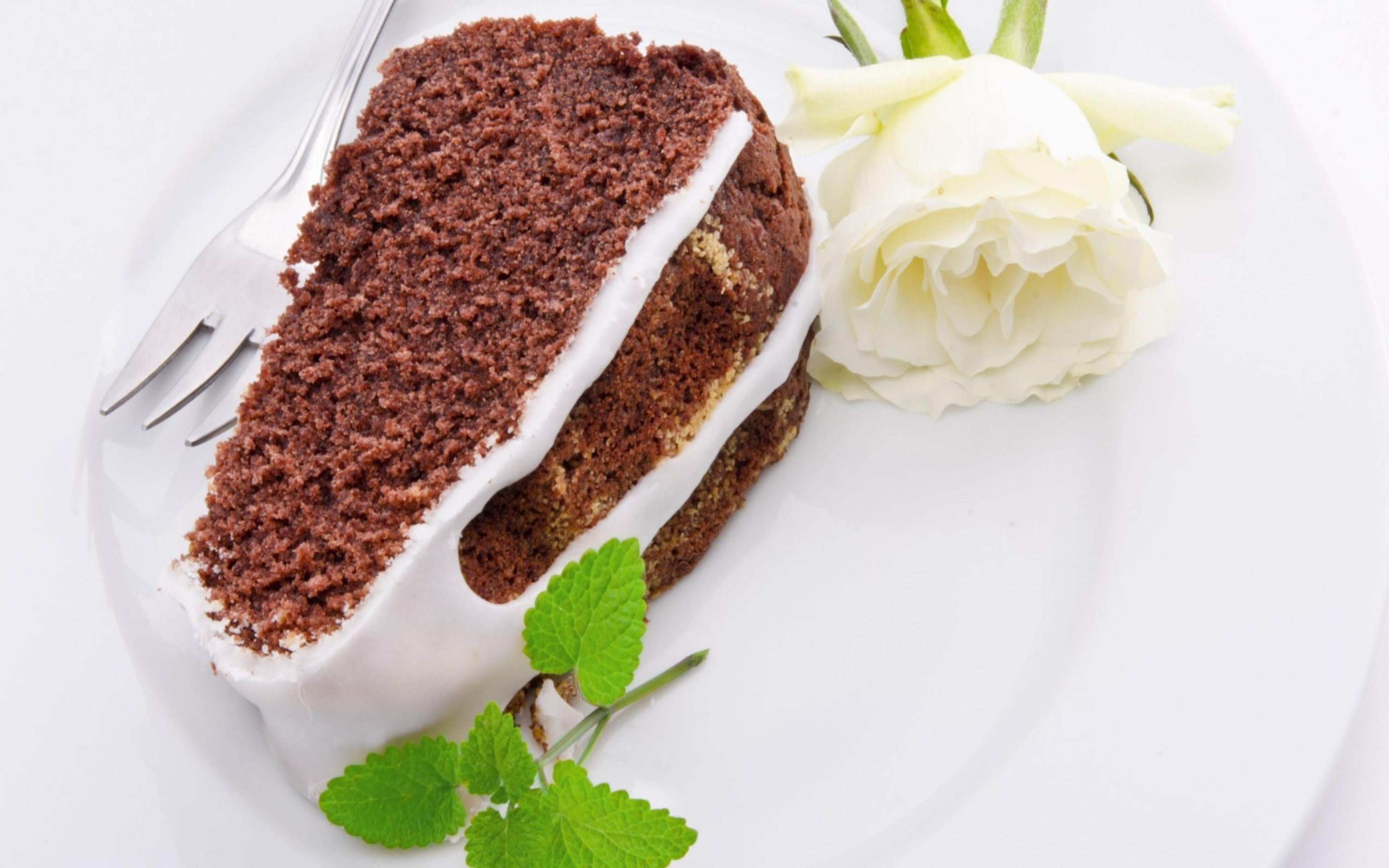 Wallpaper A piece of chocolate cake on a plate with a white rose