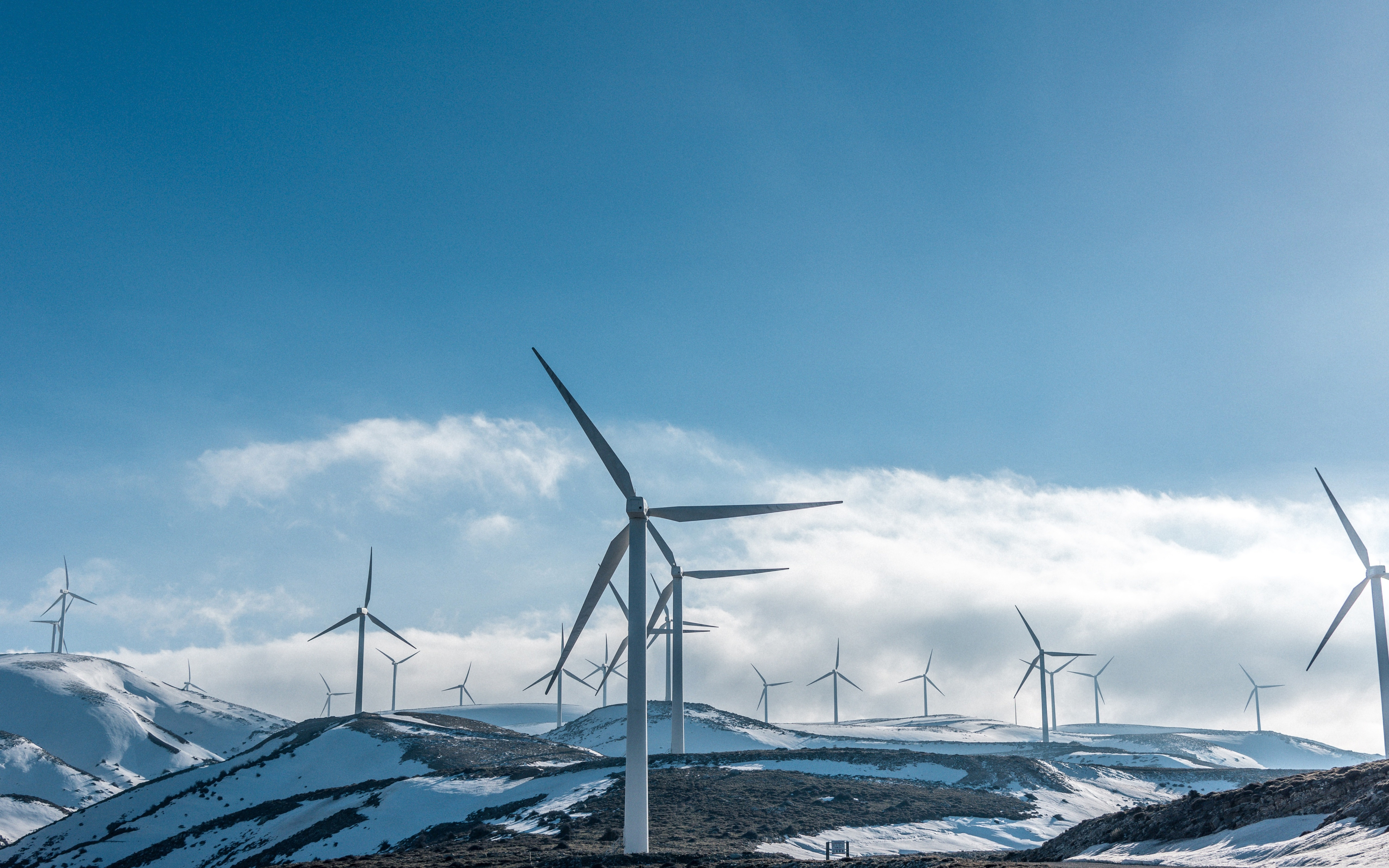Wallpaper Large wind turbines on snowy slopes